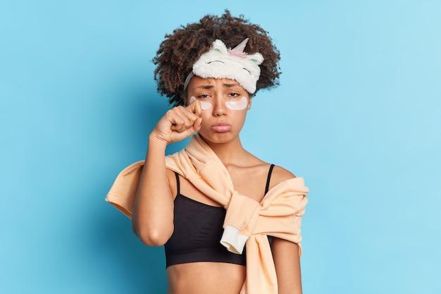 かなり動揺した巻き毛のアフロアメリカ人女性が目をこすり、欲求不満を感じ、眠そうな表情が適用されますコラーゲンパッチが朝早く目覚め、青い壁にポーズ