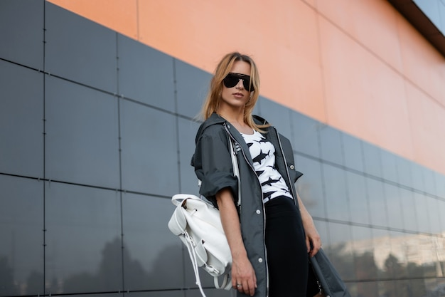 현대적인 건물 근처 야외에서 포즈를 취하는 패턴으로 흰색 티셔츠에 유행 선글라스에 세련된 재킷에 붉은 머리를 가진 꽤 도시 젊은 여자. 도시에서 아름 다운 여자 모델입니다.