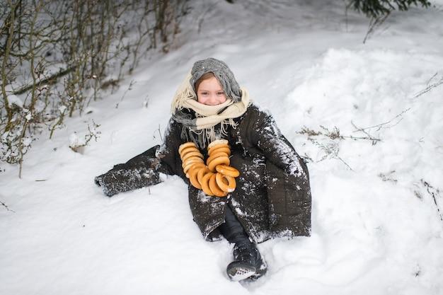 예쁜 마을 소녀는 겨울에 말린 고리 모양의 롤과 미소로 눈 숲에 서 있습니다.
