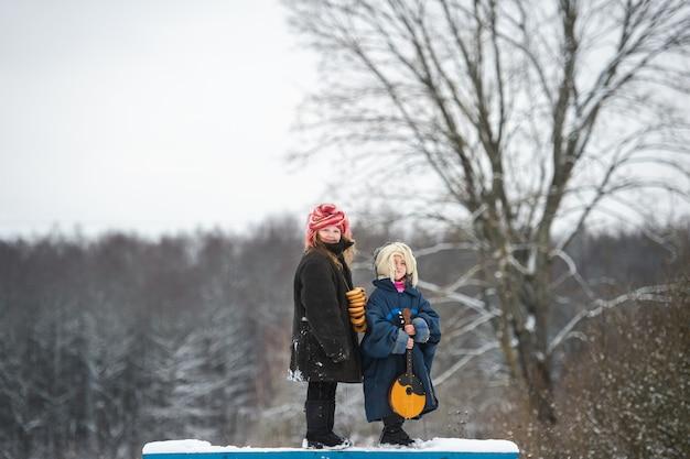 可愛らしい村の姉妹がバラライカと乾いたリング状のロールサンドでベンチに立ち、冬には母親と一緒に微笑む