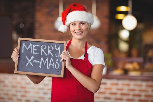 Pretty waitress with a chalkboard merry x-mas