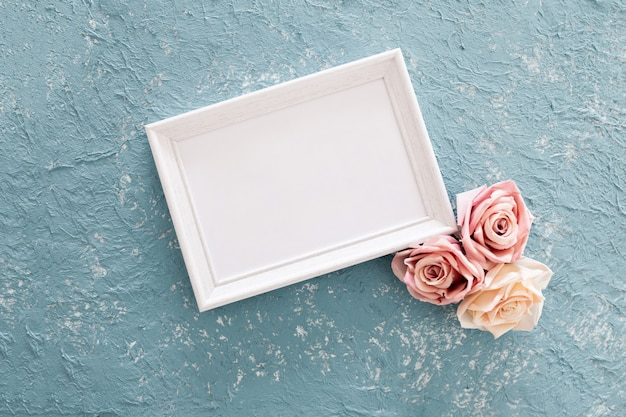 Pretty wedding frame with roses on blue textured background