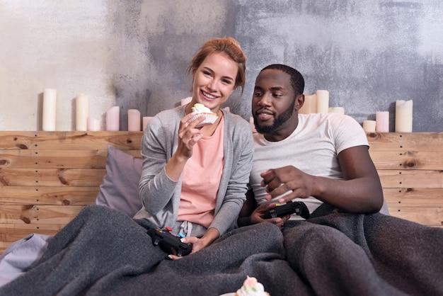 Хорошие выходные. счастливая пара молодых международных, играя в видеоигры и едят кексы, лежа в постели вместе.