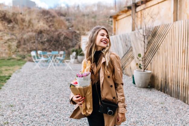 トレンディな茶色のコートを着たかなり白いヨーロッパの女の子が、紙袋での買い物で買い物から戻ってきました。