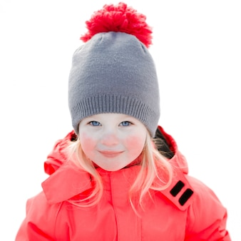 A pretty white girl in a knitted winter hat and pink jumpsuit, smiling and laughing in the snow . portrait close-up , isolated