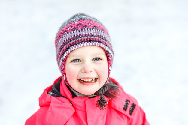 A pretty white girl in a knitted winter hat and pink jumpsuit, smiling and laughing in the snow.