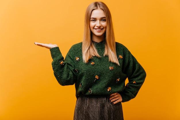 Donna abbastanza bianca con l'acconciatura dritta che ride sull'arancio. modello femminile europeo ventoso in maglione verde godendo di ritratti.