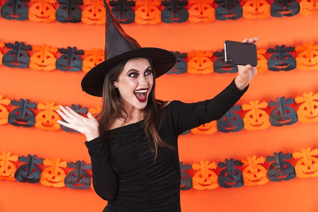 Pretty witch girl in black halloween costume taking selfie photo on smartphone isolated over orange pumpkin wall