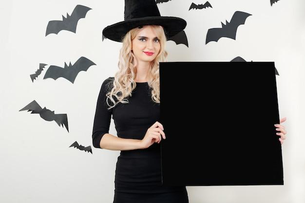 Красивая ведьма держит пустую доску
