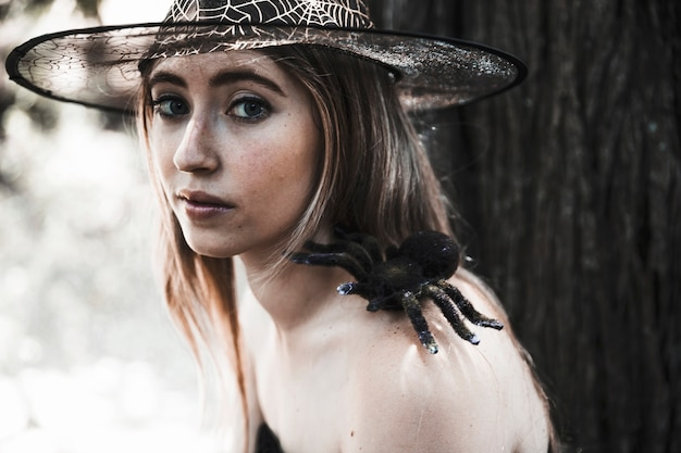 Pretty witch with spooky spider in forest daytime