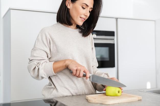 Красивая женщина 30 лет готовит завтрак с овсянкой и фруктами, стоя на современной кухне дома