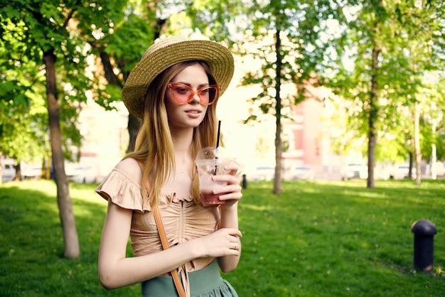 きれいな女性が公園のライフスタイルで飲み物とグラス