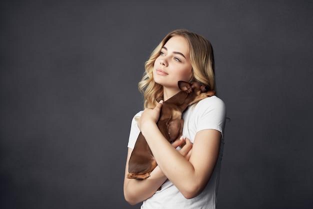 きれいな女性の小さな犬の楽しみスタジオ分離された背景。高品質の写真
