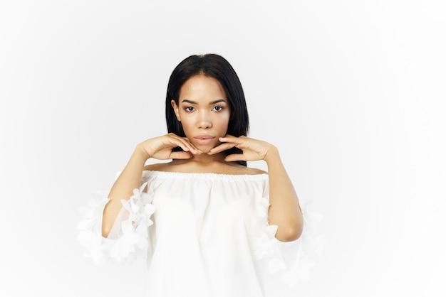 グラマーポーズのきれいな女性のアフリカの外観の化粧品は、顔の近くで手を握ります