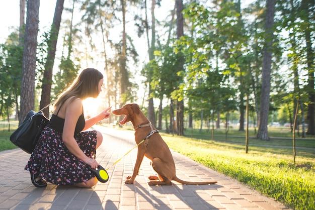 Милая женщина и красивая молодая собака в парке на езде против на восхода солнца.