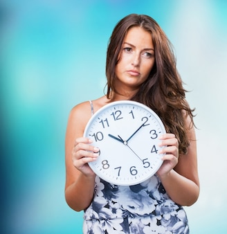 Pretty woman angry holding a clock