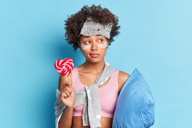 きれいな女性が目の下にコラーゲンパッチを適用して睡眠の準備をします枕を保持し、青い壁に隔離されたナイトウェアに身を包んだおいしいキャンディーは思慮深く脇に見えます