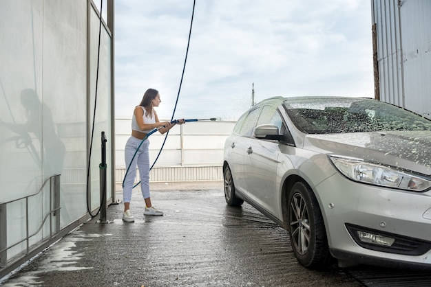 Pretty woman applies foam to automobile  from high-pressure hose