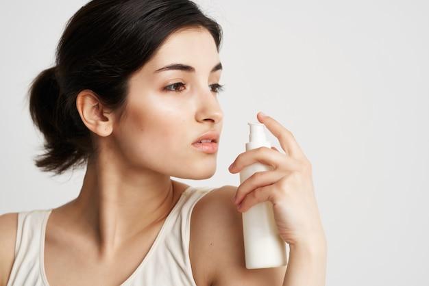 Pretty woman applying cream clean skin close-up spa treatment. high quality photo