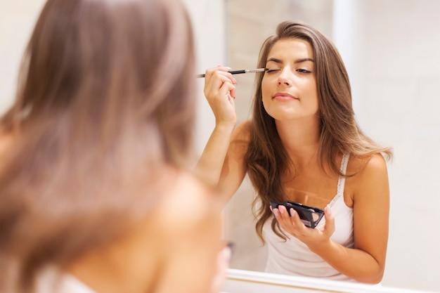 Bella donna che applica ombretto davanti a uno specchio