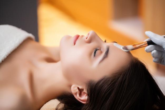 Pretty woman applying face mask at spa salon