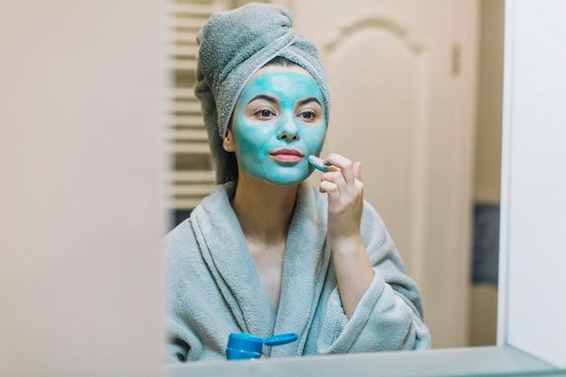 Donna graziosa che applica maschera vicino allo specchio ...