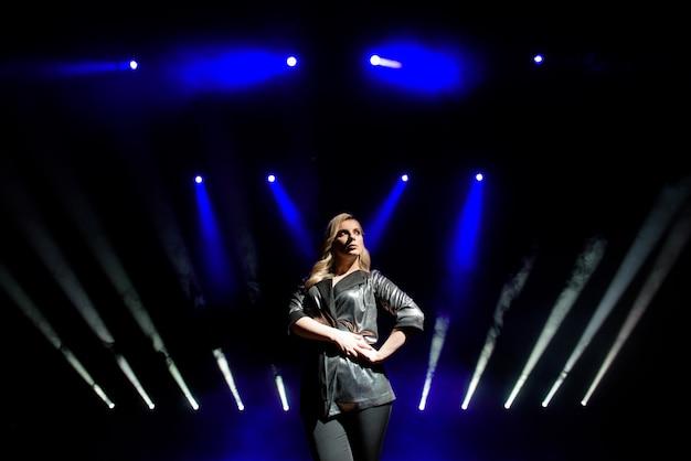 ステージ上のぼやけたスポットライトの背景の上のきれいな女性アーティスト
