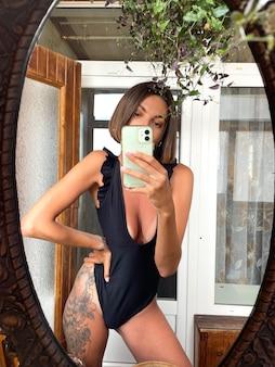집에서 예쁜 여자는 검은 색 여름 수영복을 입고 소셜 미디어의 이야기와 게시물을 위해 휴대 전화의 거울에 사진 셀카를 찍습니다.