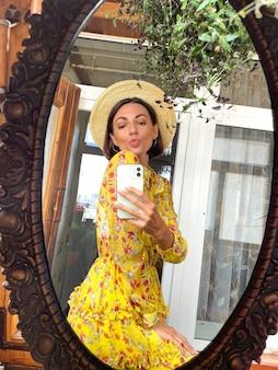 집에서 예쁜 여자는 밝은 노란색 여름 드레스와 모자를 쓰고 소셜 미디어의 이야기와 게시물을 위해 휴대 전화의 거울에 사진 셀카를 찍습니다.