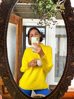 집에서 예쁜 여자는 아늑한 따뜻한 노란색 스웨터를 입고 소셜 미디어의 이야기와 게시물을 위해 휴대 전화의 거울에 사진 셀카를 찍습니다.