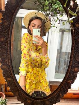 집에서 예쁜 여자는 소셜 미디어의 이야기와 게시물을 위해 휴대 전화의 거울에 사진 셀카를 찍습니다.
