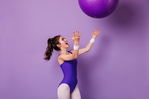 Pretty woman athlete in purple sports bodysuit in style of 80s throws fitball on isolated wall