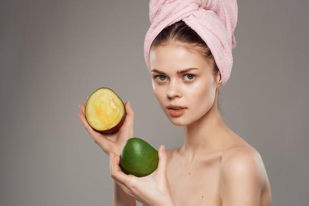 きれいな女性の裸の肩は手でトリミングされたビューで肌のマンゴーをきれいにします。高品質の写真