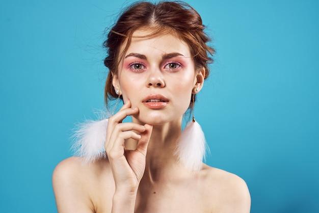 예쁜 여자 벌거 벗은 어깨 솜털 귀걸이 순수한 가죽 매력적인 파란색 배경