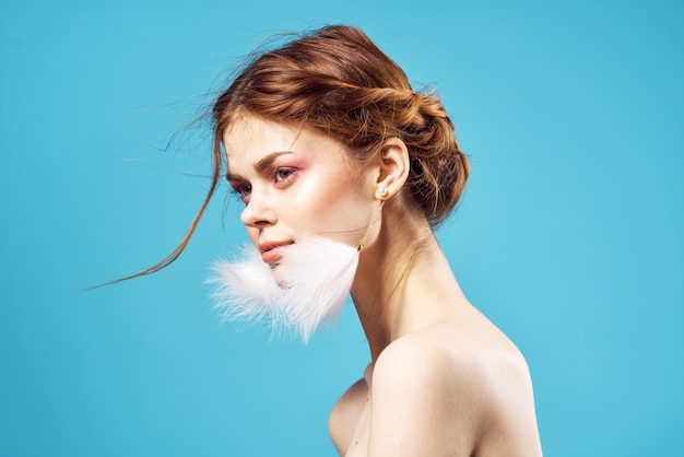 きれいな女性の裸の肩ふわふわイヤリング純革グラマーブルーの背景