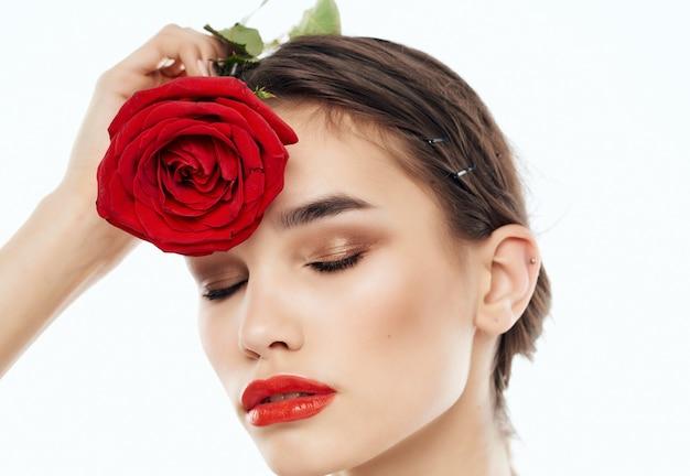 Pretty woman bare shoulders red flower clean skin posing
