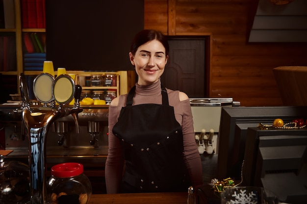 Pretty woman barista in apron behind the bar in a wooden cafeteria