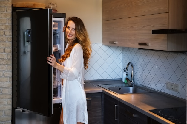 Pretty woman in bathrobe taking out the food from fridge in the morning