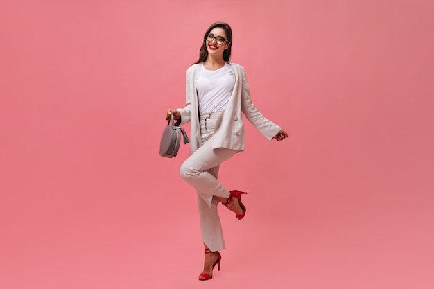 Pretty woman in beige outfit happily poses on pink background.  cheerful girl in white suit and red shoes with gray handbag is smiling.