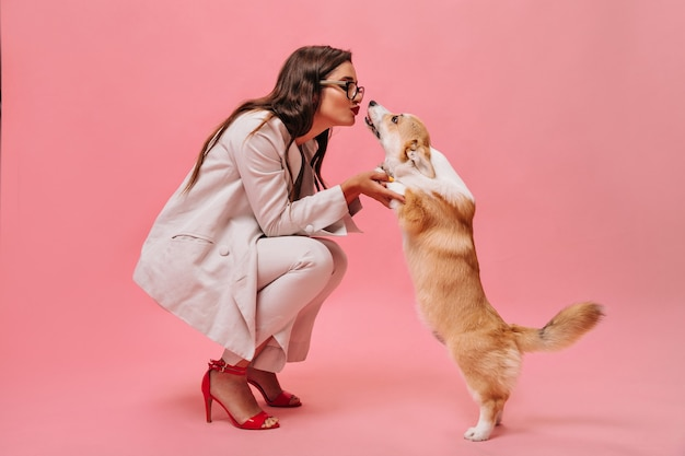 Pretty woman in beige outfit plays with dog on pink background.  cute business lady in stylish suit and red shoes kisses corgi.