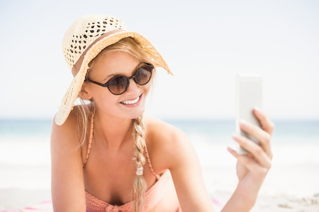 Pretty woman in bikini and sunglasses taking a selfie on the beach