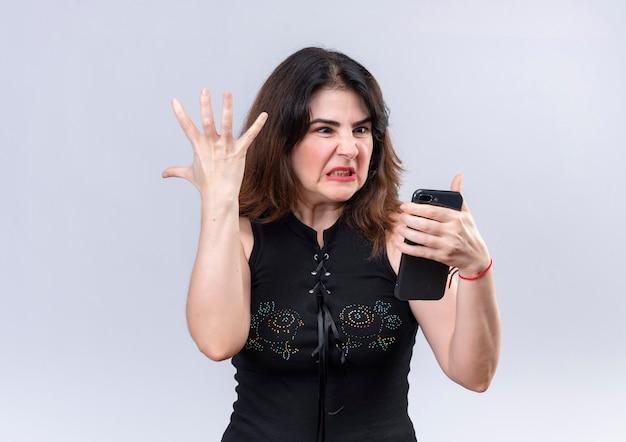Bella donna in camicetta nera arrabbiata guardando il telefono alzando il braccio