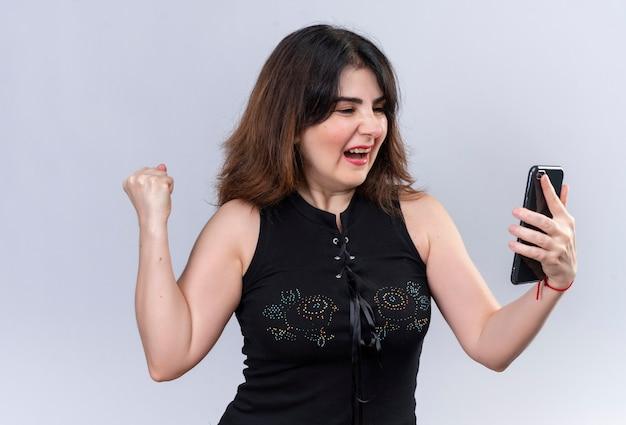 Bella donna in camicetta nera che tiene il telefono e che sembra felice per la vittoria