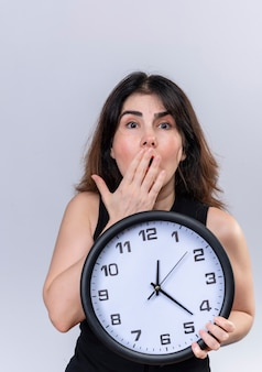 Pretty woman in black blouse looking scared for being late holding clock
