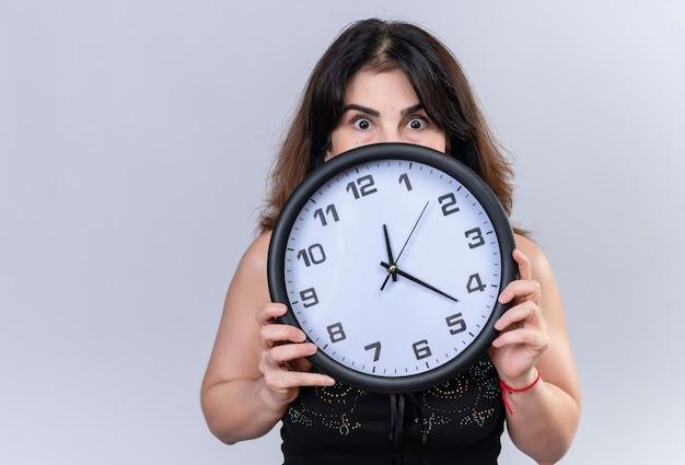 Bella donna in camicetta nera spaventata a nascondersi dietro l'orologio
