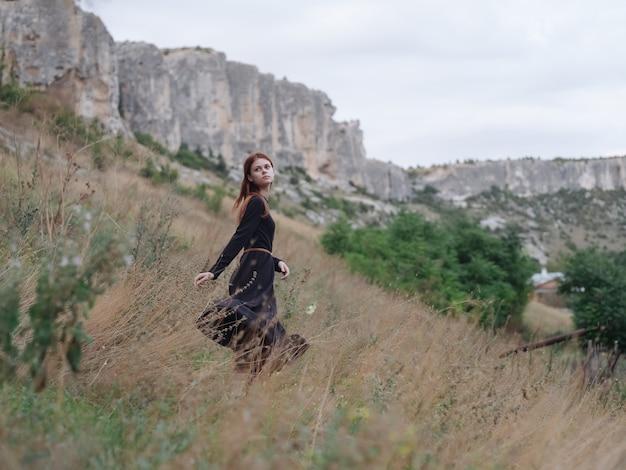 きれいな女性の黒いドレスは山の旅を歩きます
