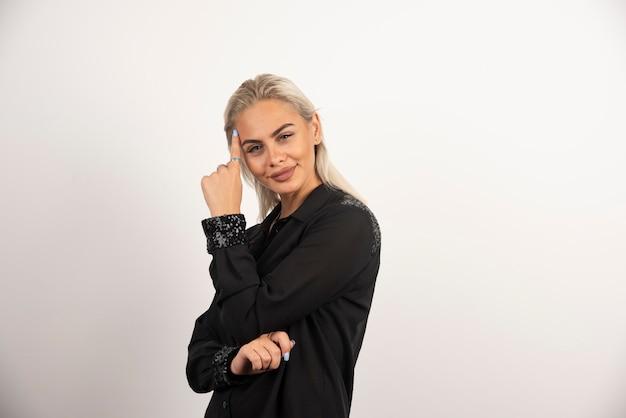 Bella donna in camicia nera in posa su sfondo bianco. foto di alta qualità