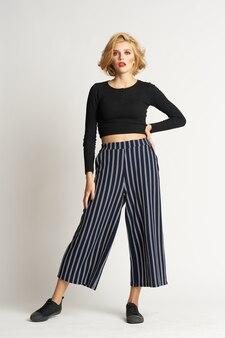 Pretty woman in black sweater striped pants fashion clothes light studio.