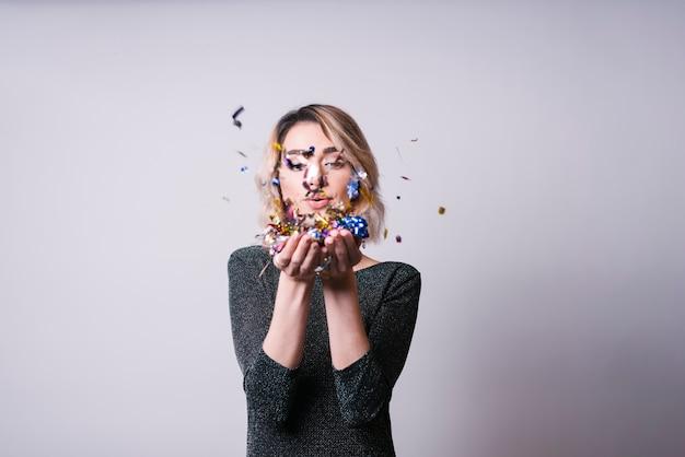 Pretty woman blowing confetti