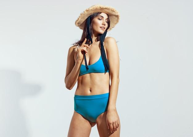 Pretty woman in blue bikini swimwear posing beach